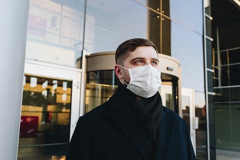 Man in face mask outside office building photo